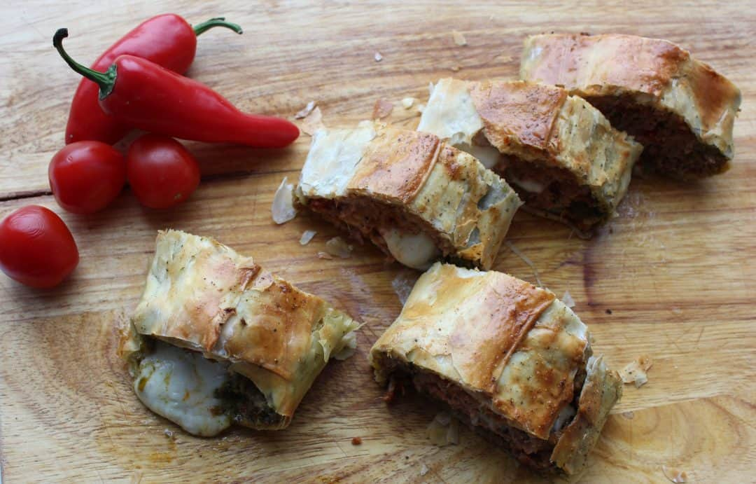 Slices of ground turkey sausage roll on a wooden cutting board