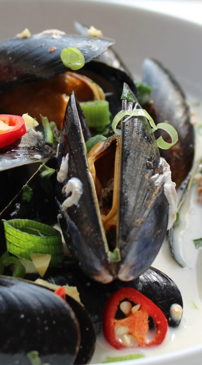Close up of Thai mussels served in a white bowl