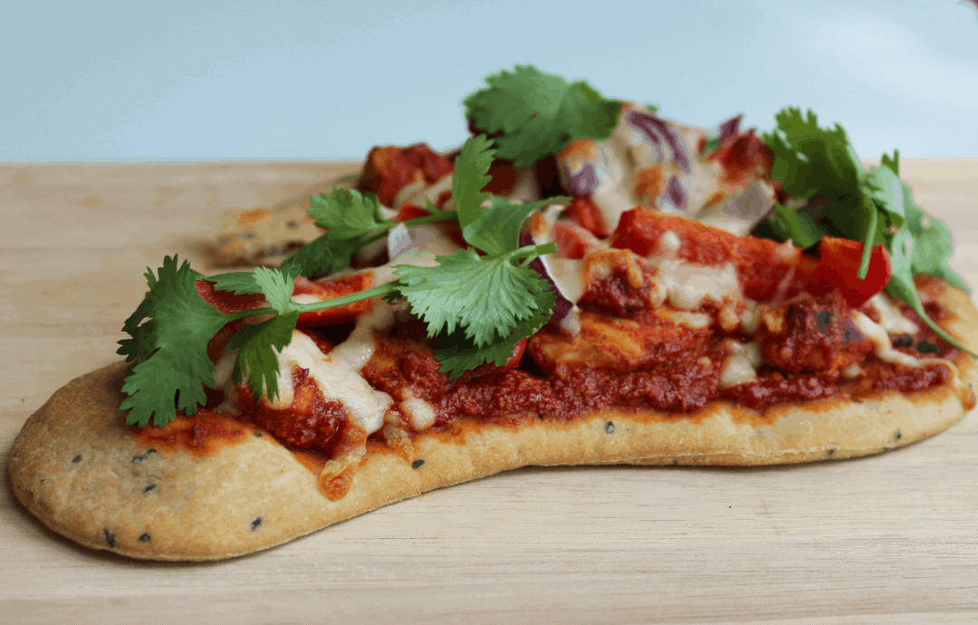 Naan bread topped with corriander on a wooden chopping board