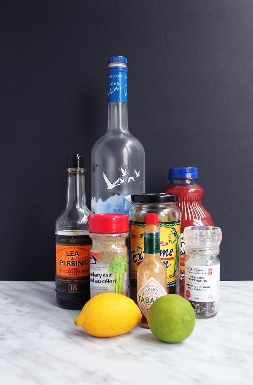 The ingredients for a classic Caesar drink. Vodka, worcestershire sauce, celery salt, pickled beans, tabasco sauce, pepper, lemon, lime and clamato juice