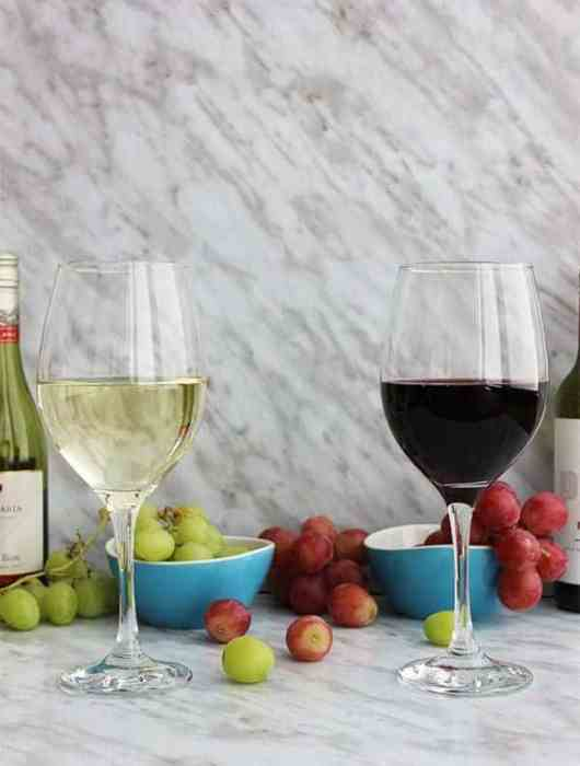 A glass of red wine and a glass of white wine on a marble backdrop