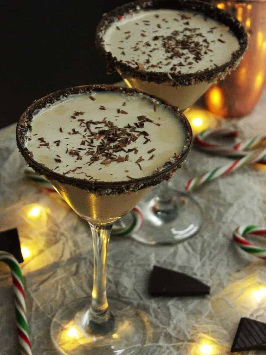 Two glasses of Christmas Candy Cane cocktail with chocolate shavings
