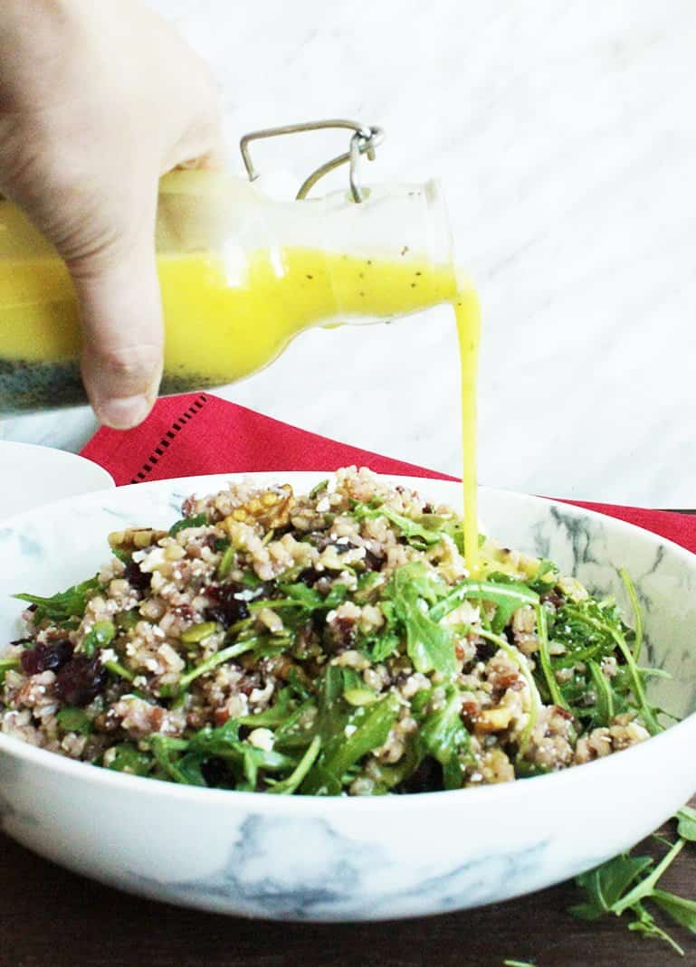 Poppy seed dressing being poured over brown rice salad