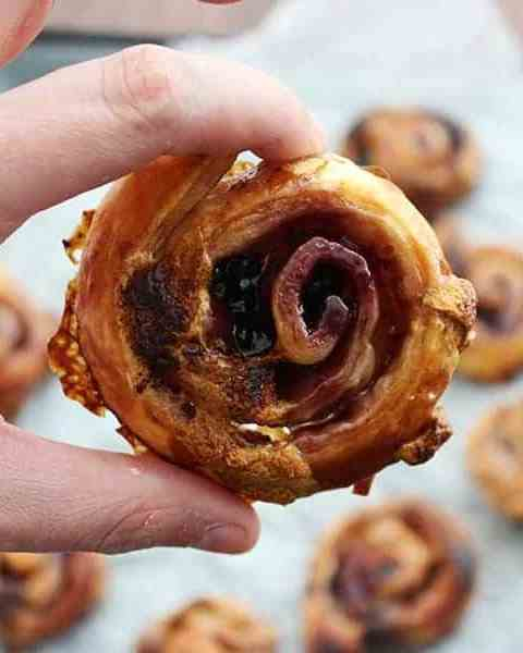 Close up of a sweet puff pastry pinwheel being held
