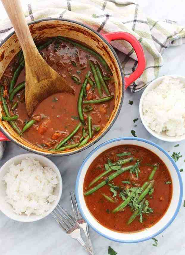 Beef curry stew with coconut milk in a large pot with wooden spoon