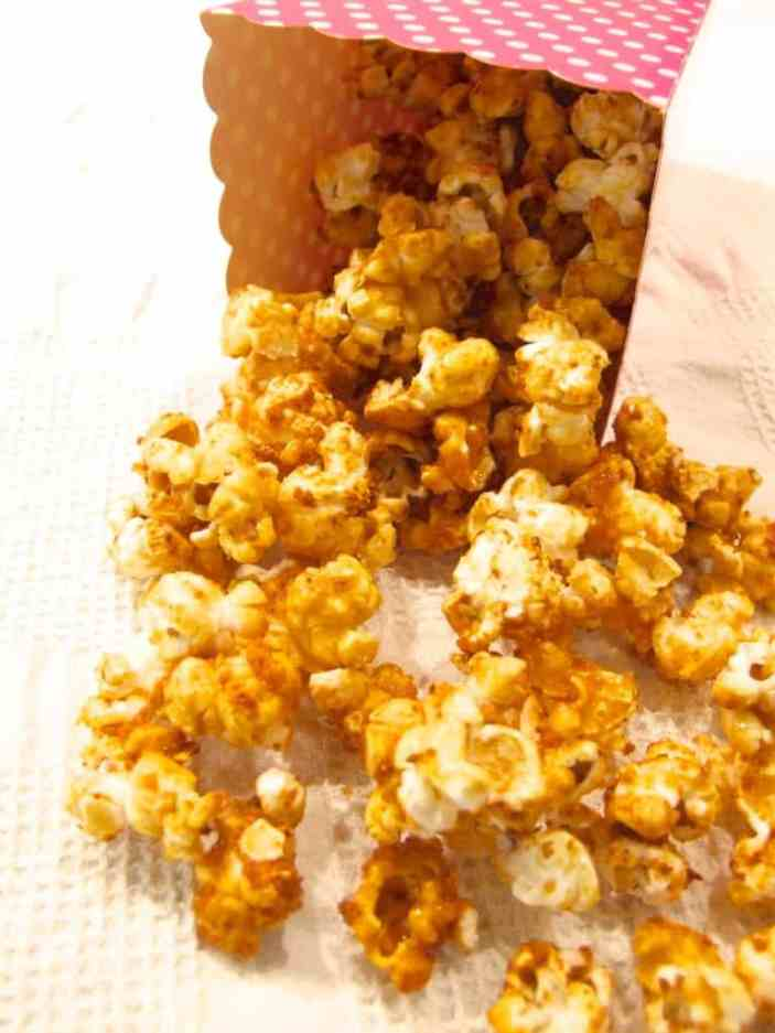 Apple and honey popcorn spilling out of a container