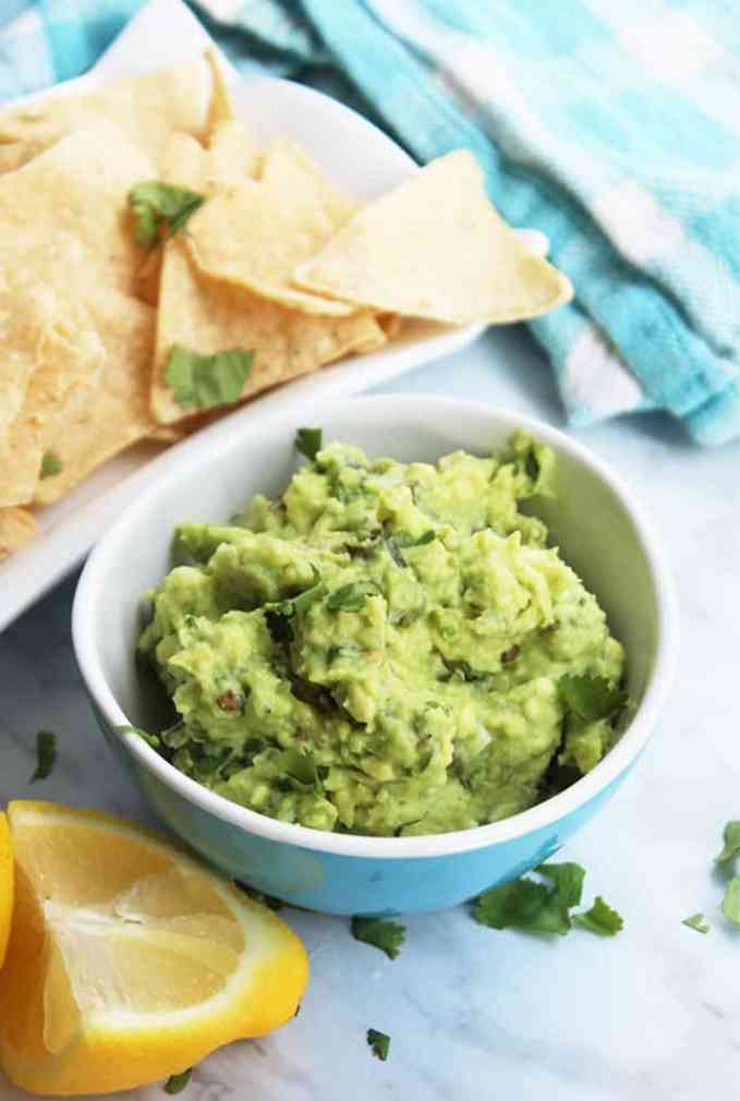 A bowl of guacamole next to a plate of tortilla chips