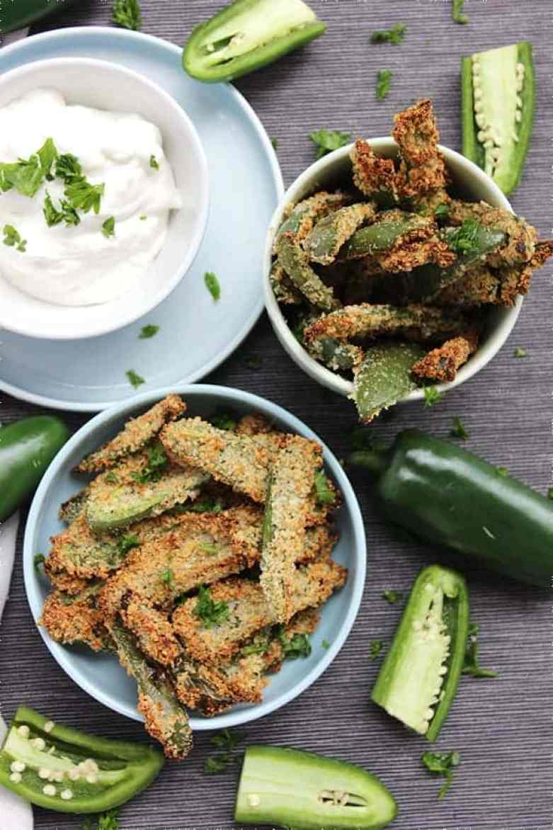 Top shot of two bowls of crispy jalapeno fries with sour cream dip and fresh herbs