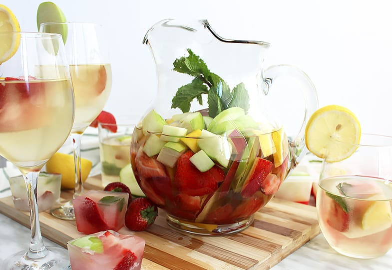 A jug of white wine sangria on a board with wine glasses