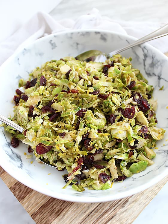 Sauteed Brussels sprouts in a serving bowl with spoons