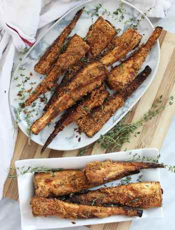 Top shot of roasted parsnips with parmesan on two plates with fresh herbs