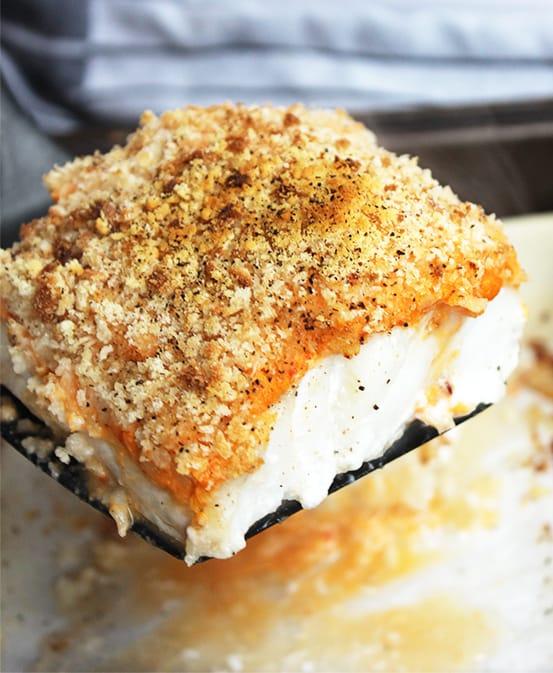 A piece of crispy baked cod on a spatula