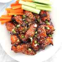 Wings topped with sesame seeds and green onions on a white plate