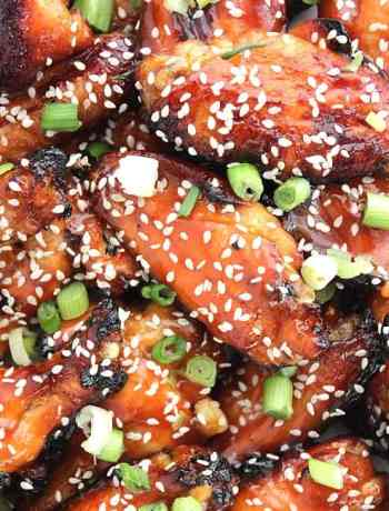 Close up of the sticky chicken wings with a honey and sriracha glaze sprinkled with sesame seeds