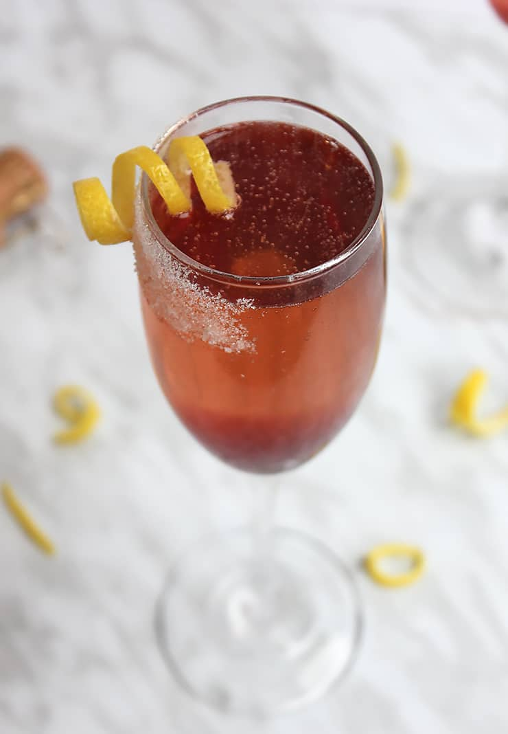 A cherry champagne cocktail garnished with lemon peel