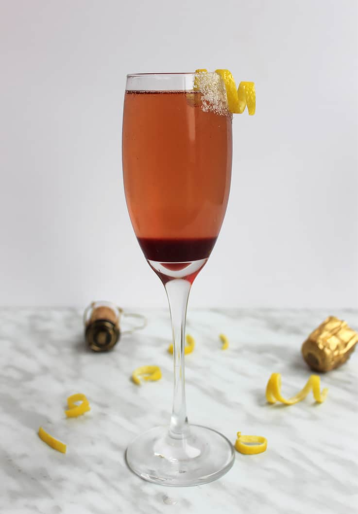 A cherry champagne cocktail next to a champagne cork