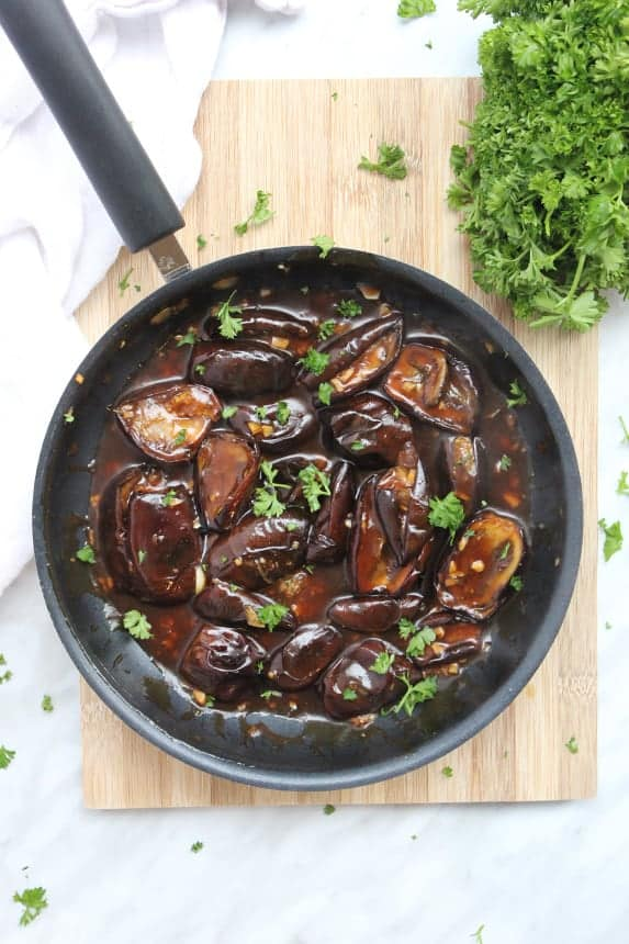 Stir fried baby eggplant in a frying pan