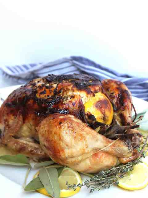 Roast chicken on a white platter with lemon and herbs