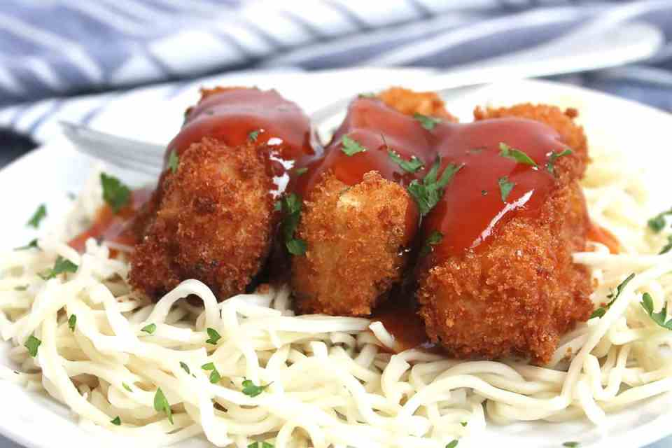 Three pieces of breaded tofu on boodles and drizzled with sauce