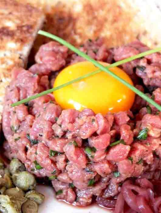 A whole egg yolk on top of steak tartare