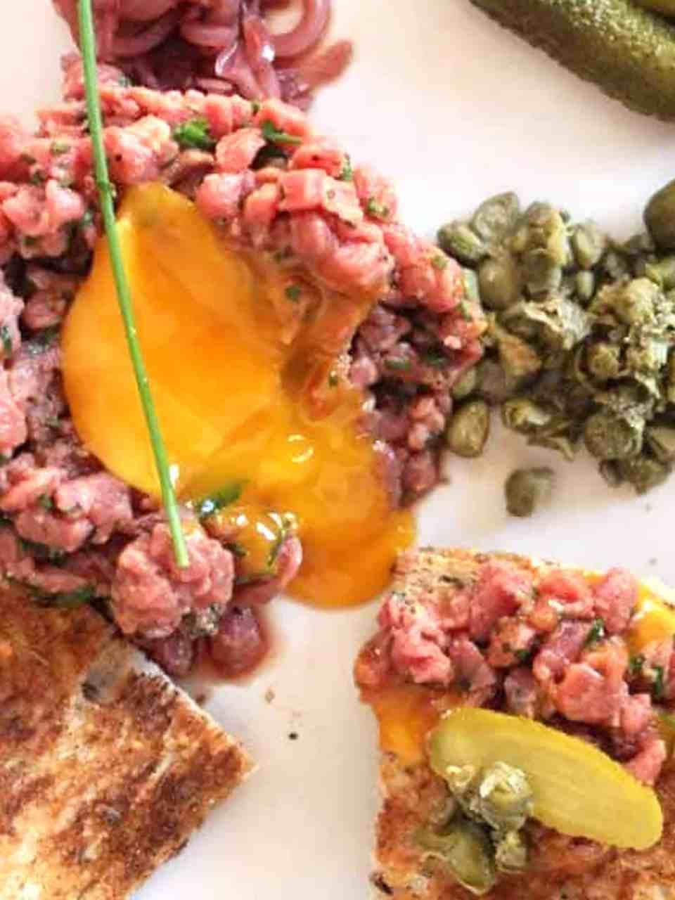 Overhead shot of the egg yolk broken in the steak tartare