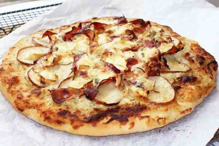 White pizza topped with pears and ham on a piece of parchment paper