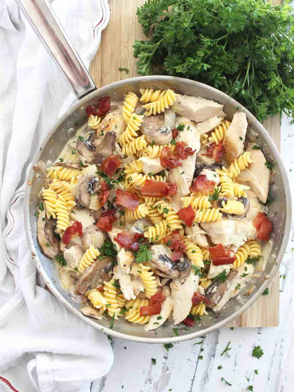 Overhead shot of chicken mushroom pasta in a skillet garnished with fresh herbs.