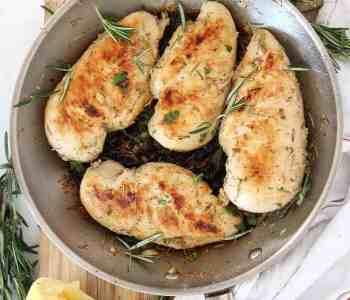 Four cooked lemon rosemary chicken breasts in a skillet.