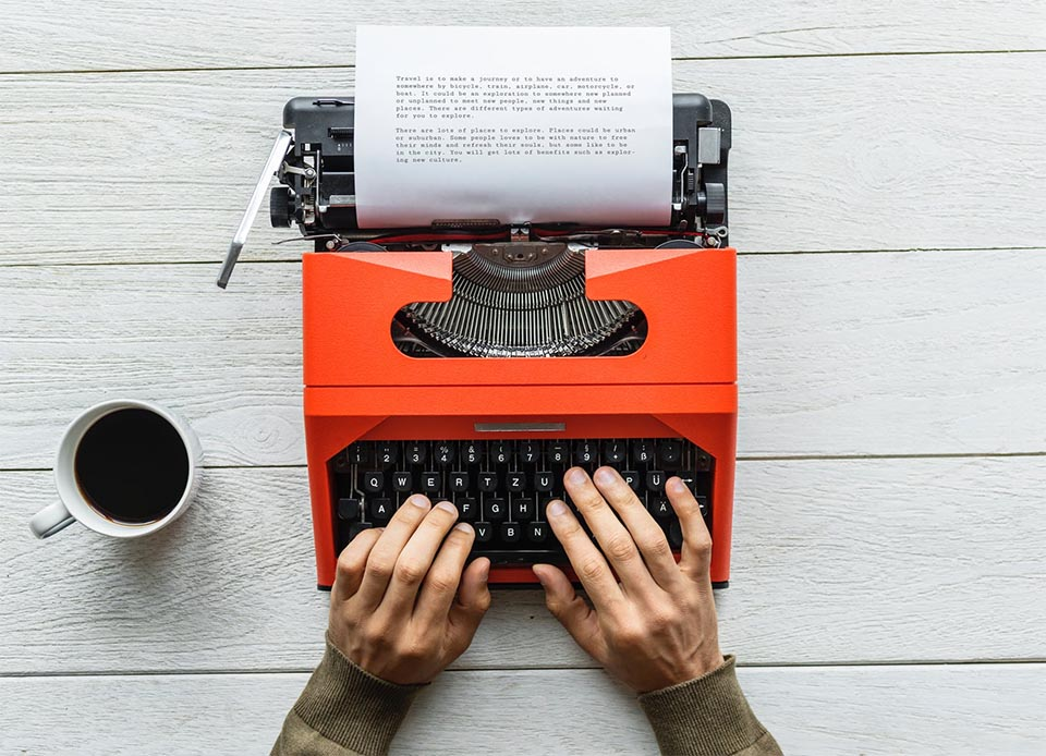 Someone typing on a typewriter to create a story