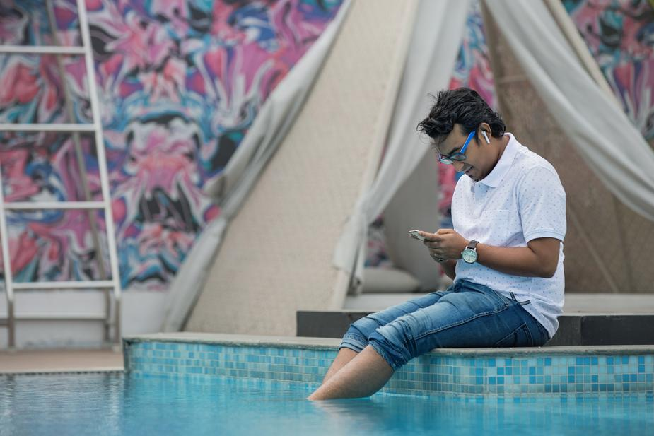 Example of a diverse stock photo of man sitting down by a pool checking his phone