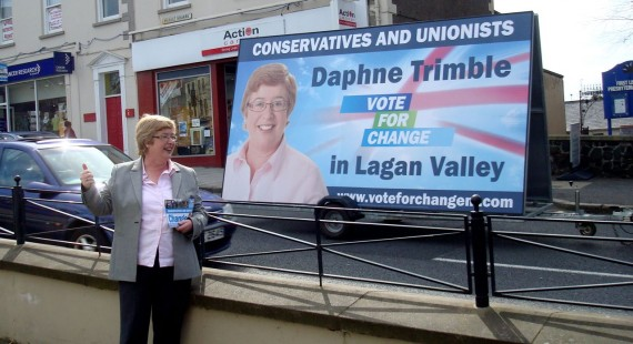 Daphne Trimble posing in front of an election poster mounted on a trailer