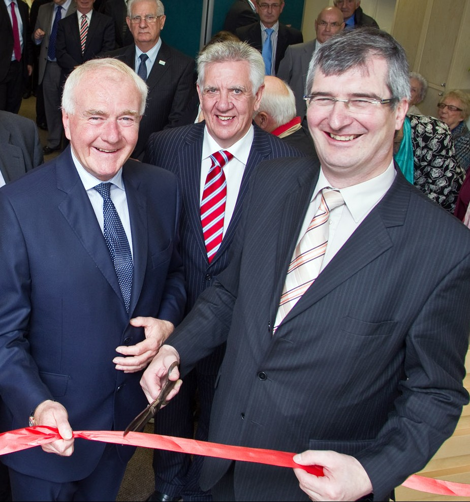 Tom Eliott wielding scissors at the opening of David McNarry's Saintfield Advice Centre Opening