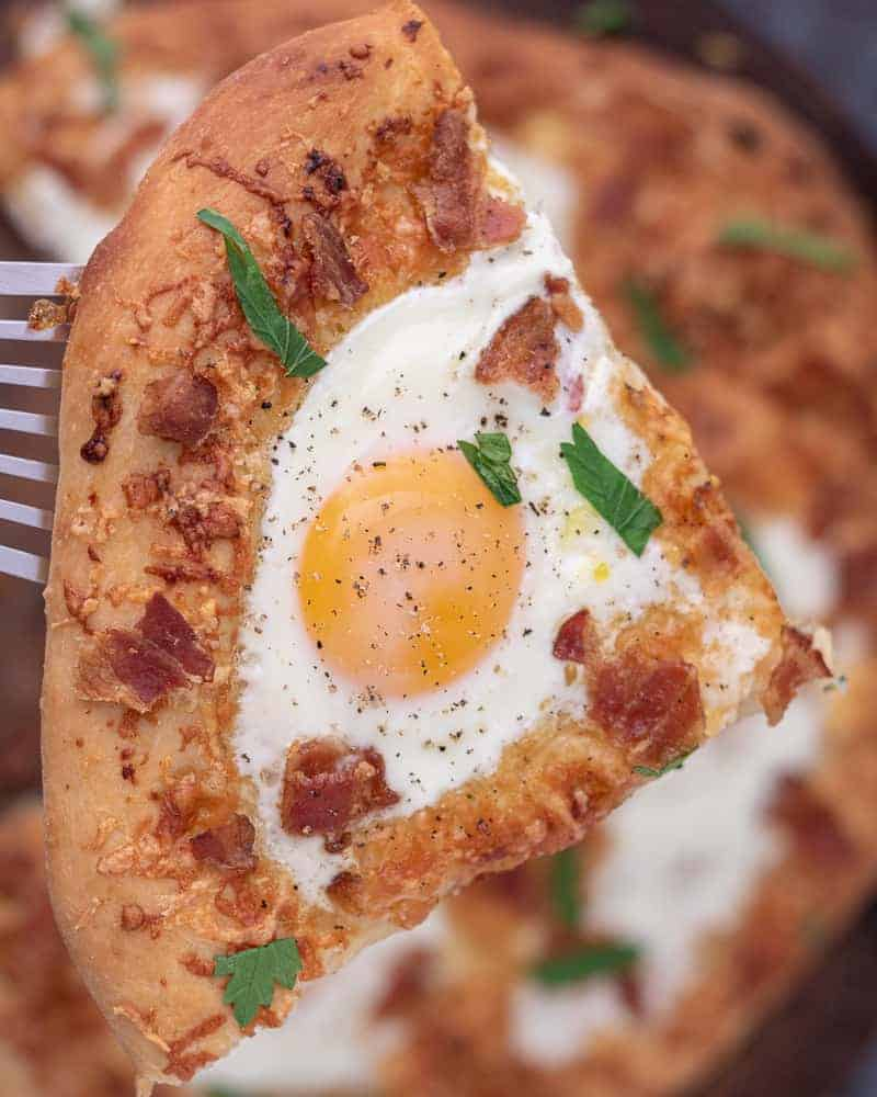 Close up of breakfast pizza with an egg yolk