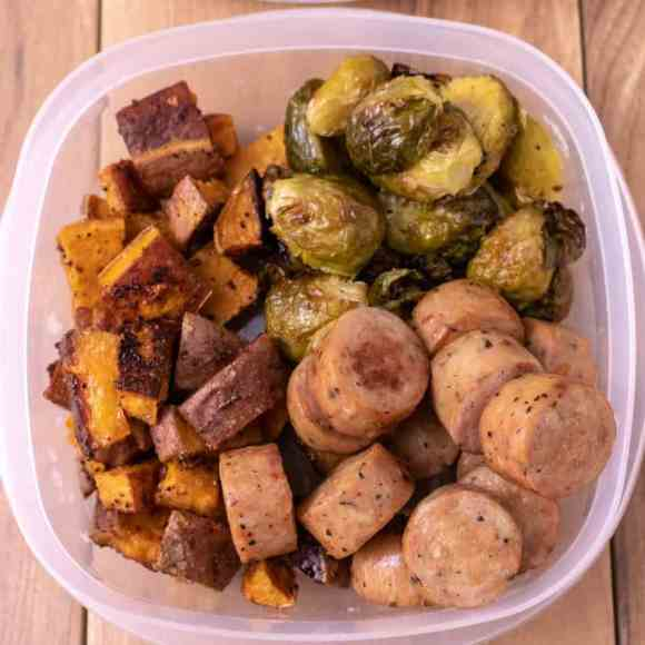Overhead shot of chicken sausage cut into coins, roasted brussel sprouts and roasted sweet potatoes in a clear plastic container. On a wood back ground