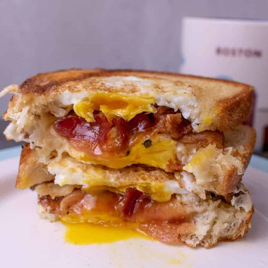 A sandwich cut in half to show runny yolks, bacon and cheese.