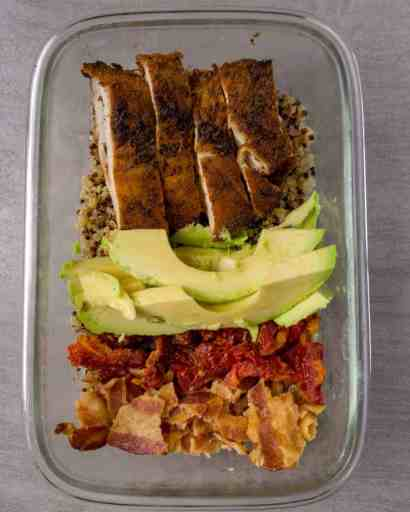 Roasted Turkey, sliced avocado, chopped sundried tomatoes, crumbled bacon over a bed of quinoa in a glass container.