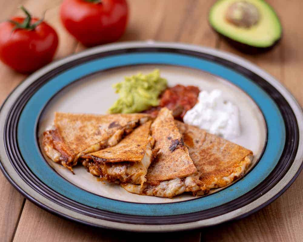 Pulled pork quesadilla with guacamole, salsa and sour cream on the plate. Behind the plate is fresh tomatoes and an avocado.