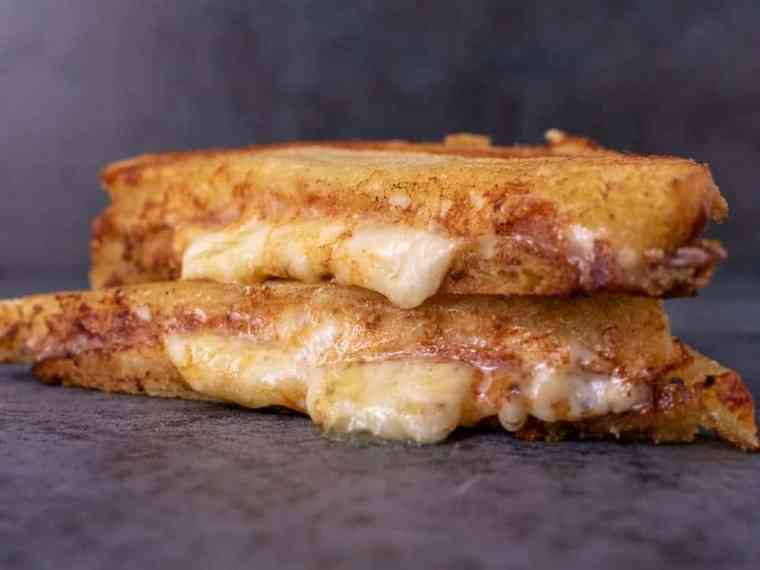 Grilled cheese, cut in half and stacked on top of each other. Cheese is oozing out.