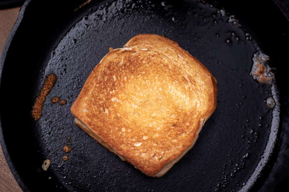 Golden brown grilled cheese on cast iron pan