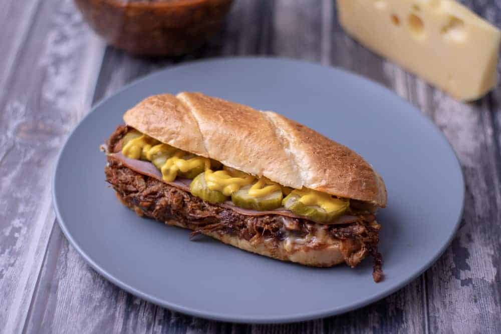 BBQ pulled pork cuban sandwich on a blue plate.