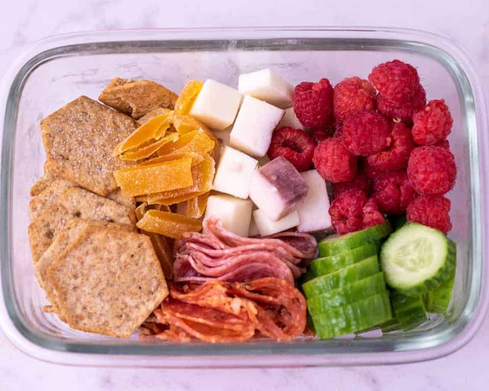 Mini Cheese plate in a take out container.