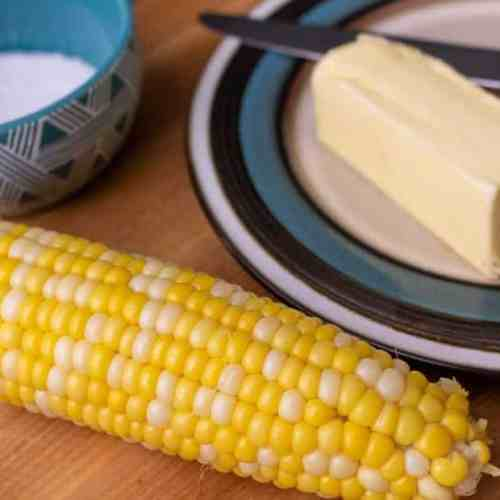 One piece of corn on the cob next to butter and salt.