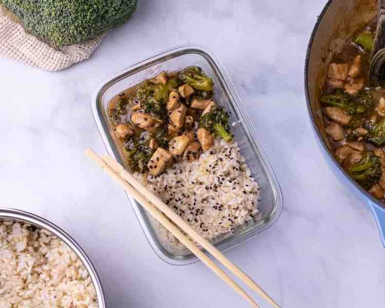 a meal prep container of chicken and broccoli in oyster sauce with broccoli in the background