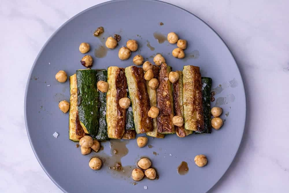 Roasted zucchini with balsamic and halzenuts on a blue plate