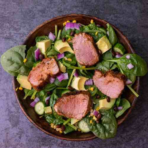 Close up of cajun pork tenderloin spinach salad in a wooden bowl
