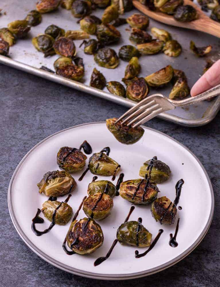 Roasted brussel sprouts drizzled with balsamic reduction. A hand with a fork is picking up a brussel sprout.