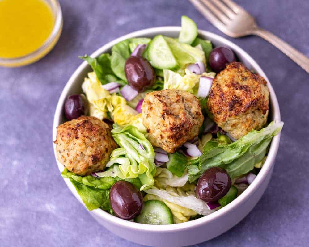 Greek meatball salad in a bowl with a fork and salad dressing