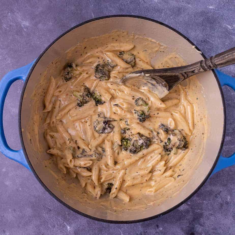 Creamy alfredo sauce in a large dutch oven pot with a wooden spoon