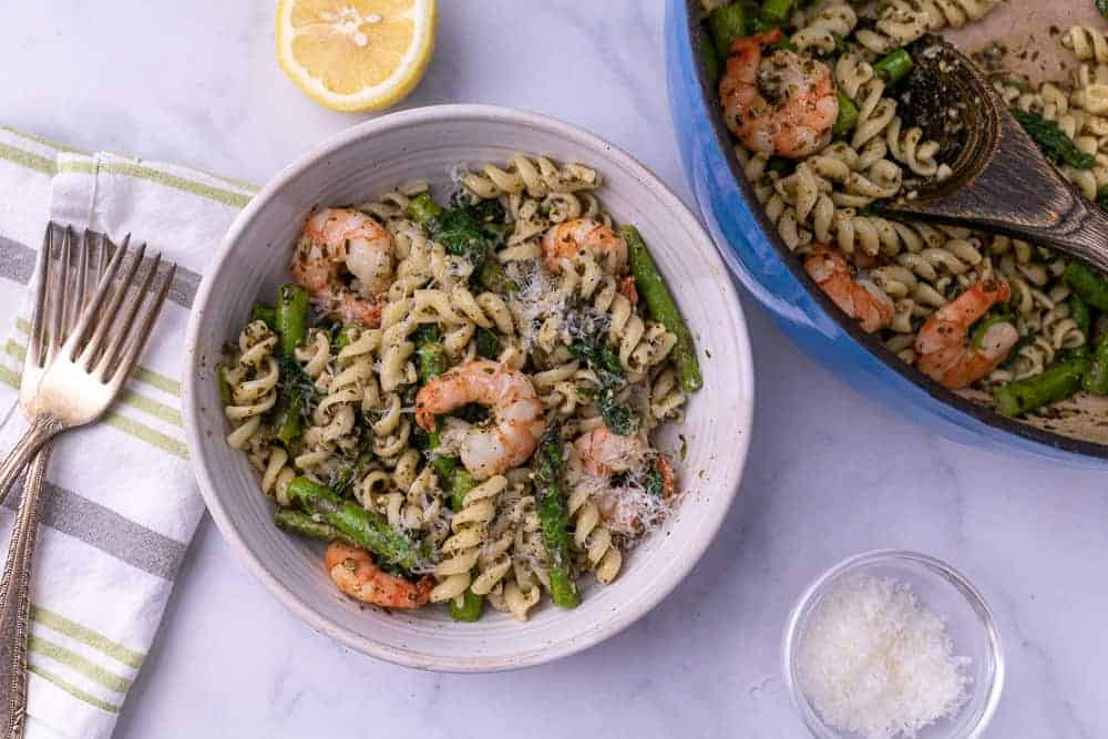 A white bowl of lemon pesto pasta with shrimp next to 2 forks and a dutch oven with parm and lemon in the background