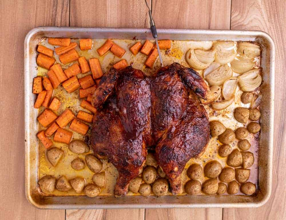 Roasted chicken on a sheet tray with vegetables.